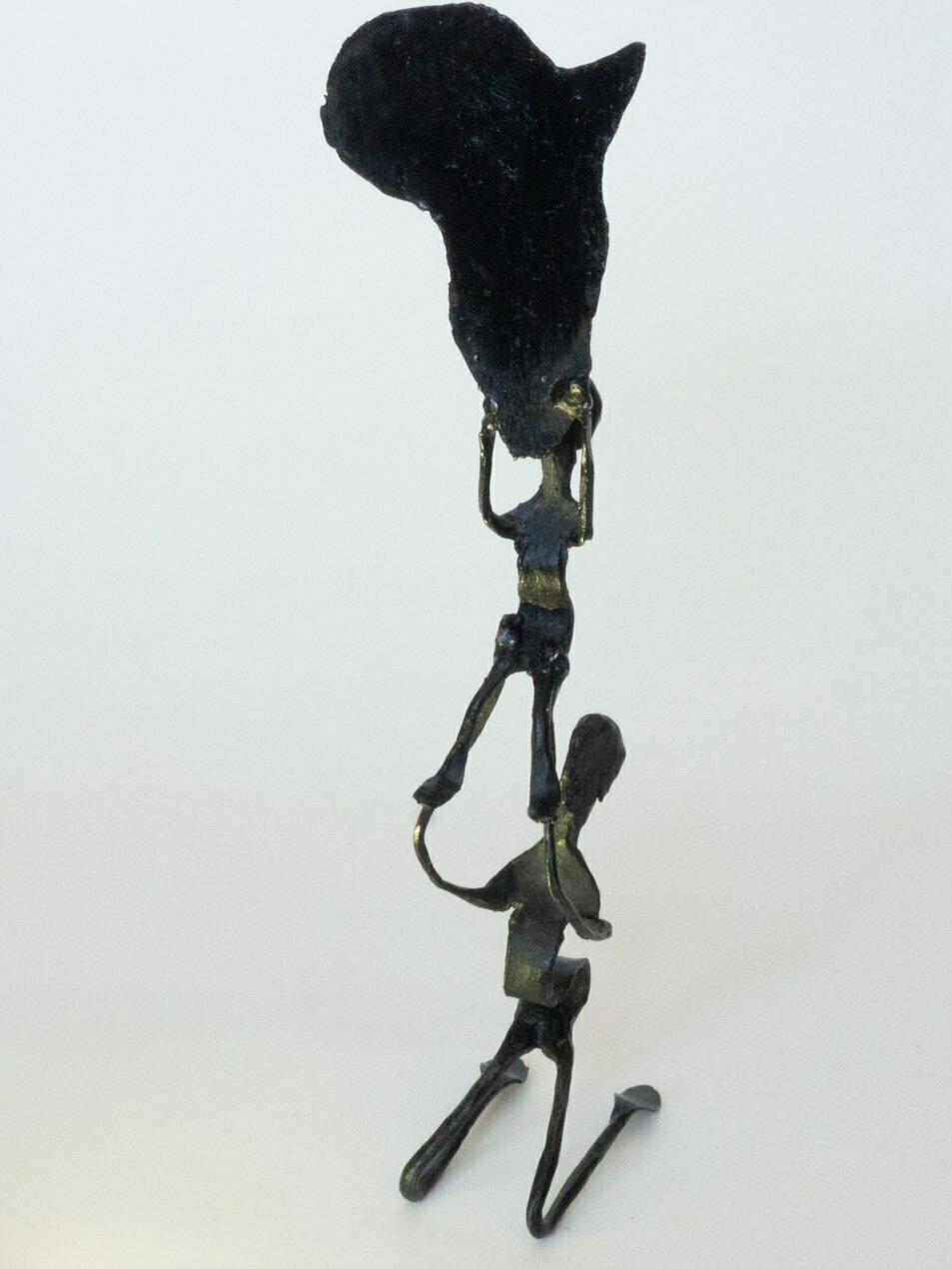 Escultura de metal pintando en negro, una figura humana sostiene a otra figura que, a su vez, sostiene el mapa del continente africano.