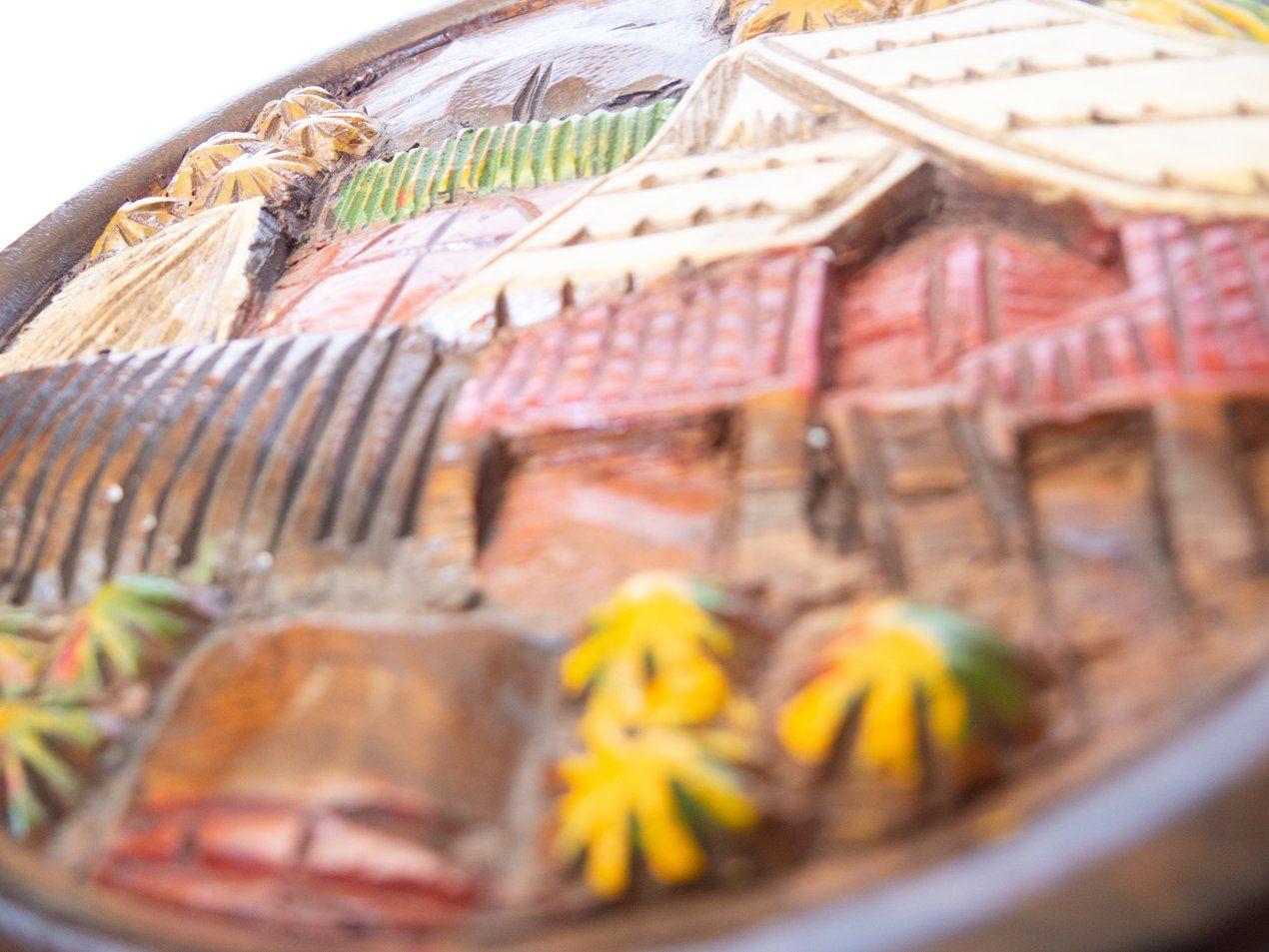 Cuadro de madera en bajo relieve aldea Cuadro de madera en bajo relieve redondo con motivo de aldea dominicana. Origen: República Dominicana. Tamaño: 25cm de diámetro.